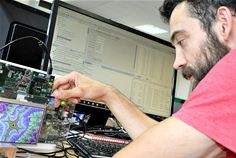 In the image, a demonstration board containing an Arm CPU generates a fractal pattern on the screen, while the engineer views the operation of the program via the GUI on his workstation